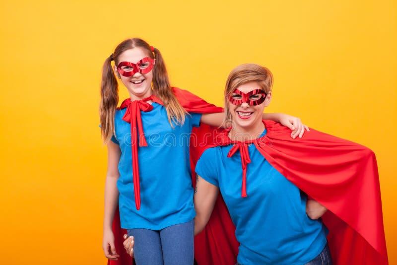 Superheromoder som rymmer hennes liten flicka på hennes arm över gul bakgrund arkivbilder