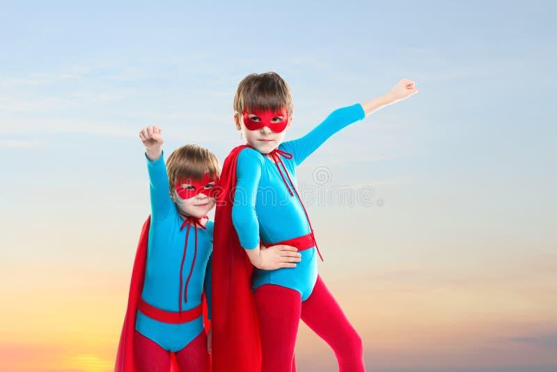 Superheropojkar på solnedgånghimmelbakgrund royaltyfri foto