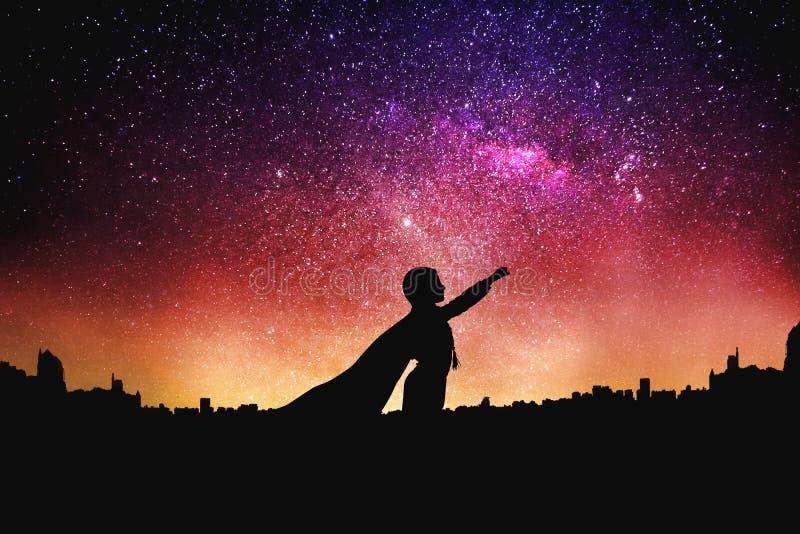 Superherosilhouet bij de achtergrond van de nacht sterrige hemel stock foto