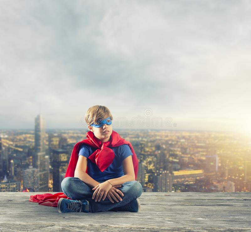 Superherounge som sitter på en vägg som drömmar royaltyfri bild