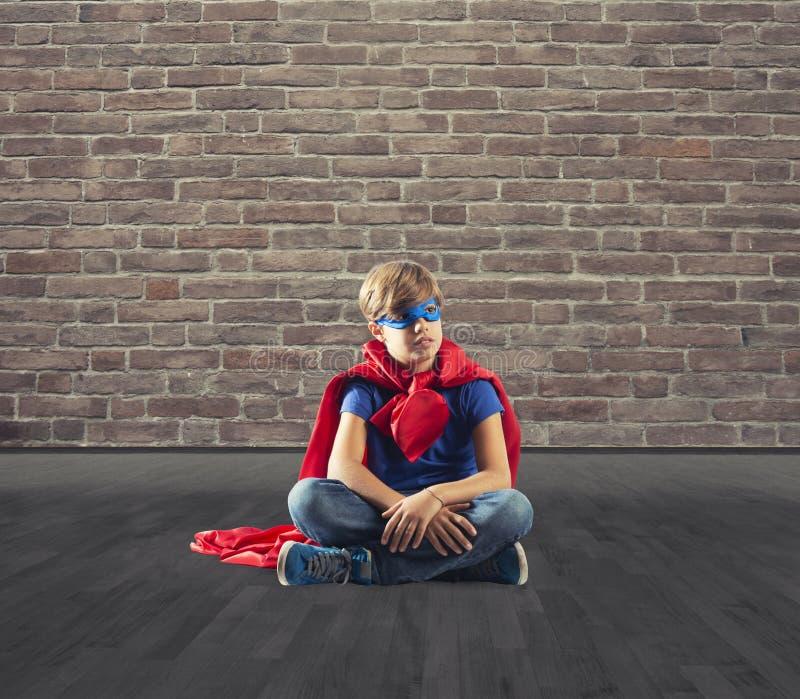 Superherounge som sitter på en vägg som drömmar royaltyfri fotografi