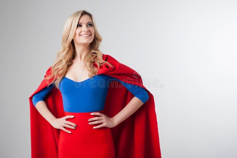 Superherovrouw Jong en mooi blonde in beeld van superheroine in het rode Kaap groeien stock fotografie