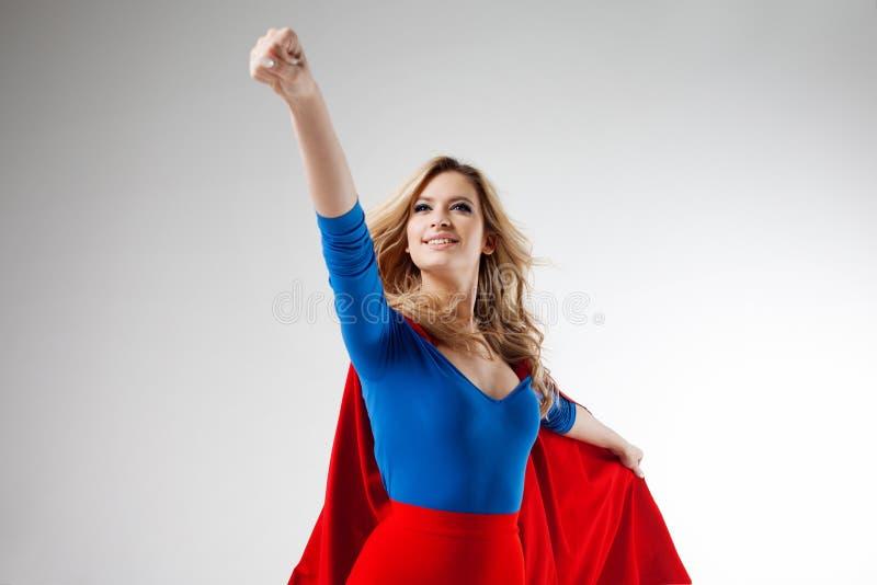 Superherovrouw Jong en mooi blonde in beeld van superheroine in het rode Kaap groeien Voorwaarts en stijgend stock foto
