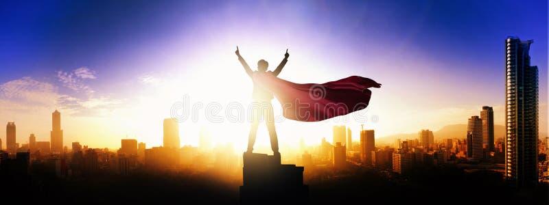 Superherozakenman die stadshorizon bekijken bij zonsopgang royalty-vrije stock fotografie