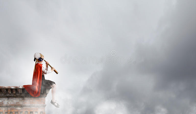 Superkid with spyglass. Cute supergirl of school age with looking in spyglass royalty free stock photos