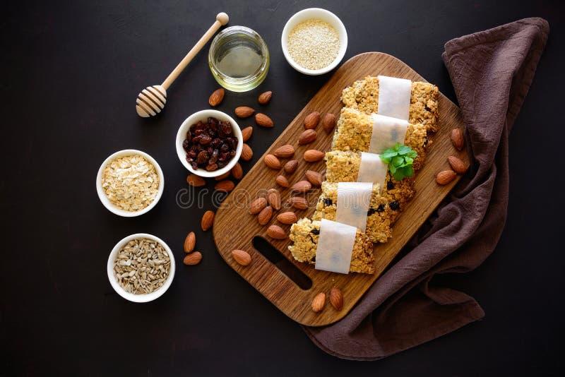 Superlebensmittelfrühstücksbar mit Hafern, indischem Sesam, Sonnenblumensamen, Honig und Nüssen auf braunem hölzernem Hintergrund lizenzfreie stockfotos