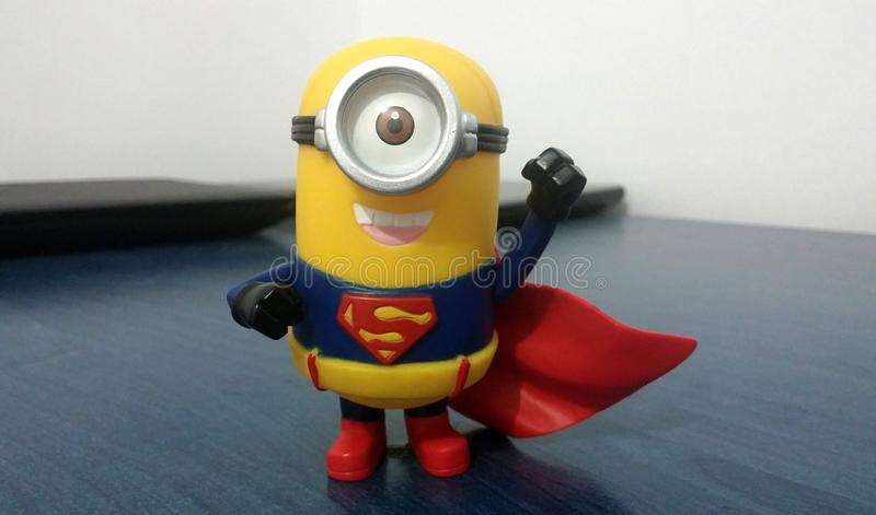 Superman Minion. Toy dressed with his blue and red suit. Red cape, superman logo, hand in the air for flying stock image