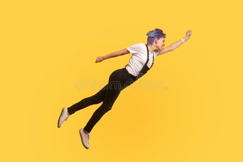 Superman Portret van een enthousiast, ambitieus hipster-meisje dat als superheld in de lucht vliegt, zich vrij voelt studio shot stock foto