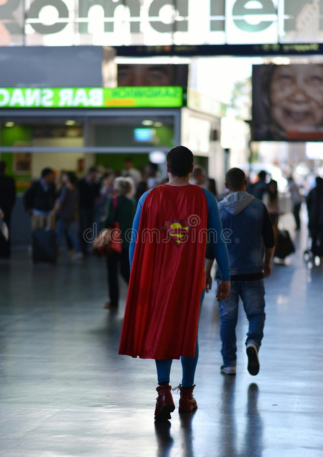 Superman in Rome. Strange man, dressed as Superman, walking through the crowd in the station Roma Termini . Italia royalty free stock photography