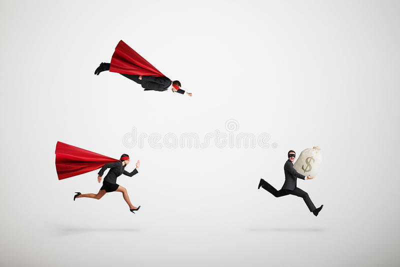 Superman and superwoman trying to catch criminals stock photography