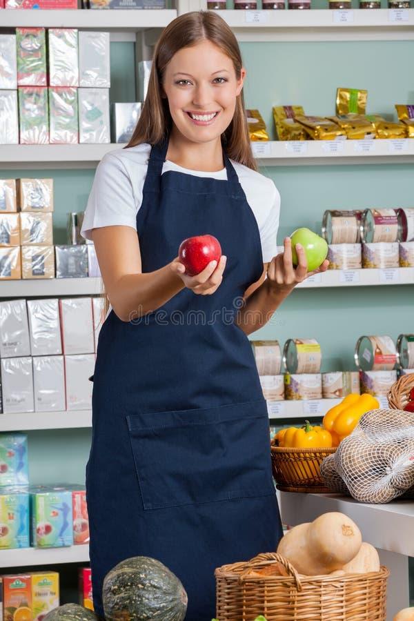 Supermarché de Holding Apples In de vendeuse image stock