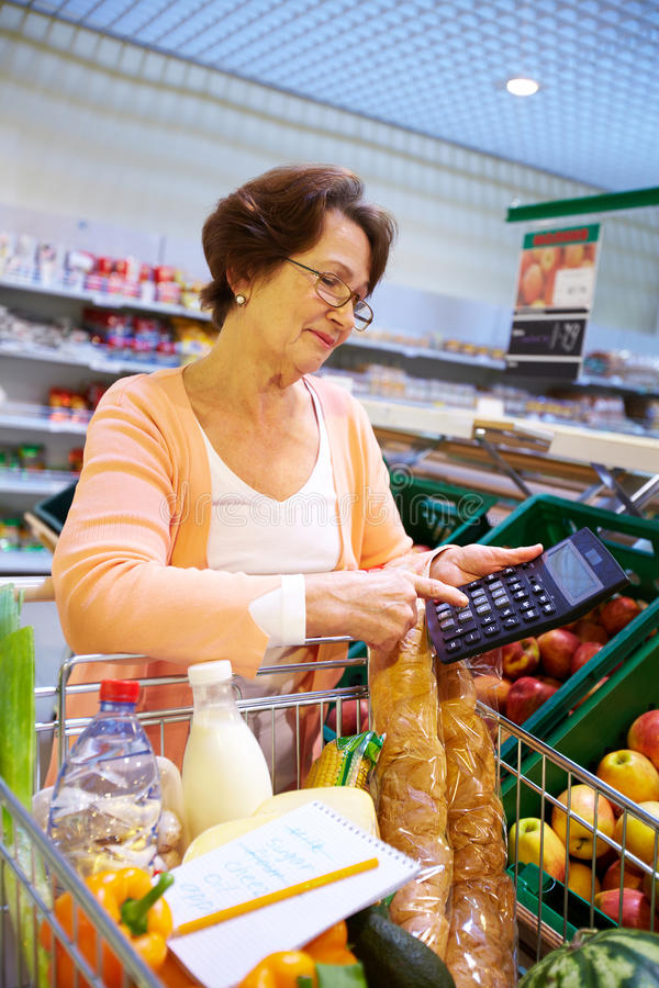 In supermarket. Image of senior woman hand touching buttons of calculator with goods in cart near by stock photos