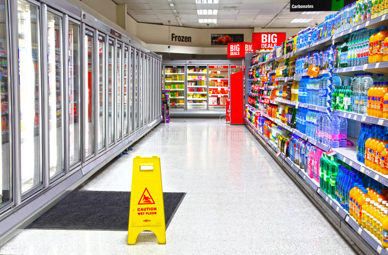 Supermarket. Freezer and drinks aisle of a supermarket with caution slippery when wet sign. Health and safety