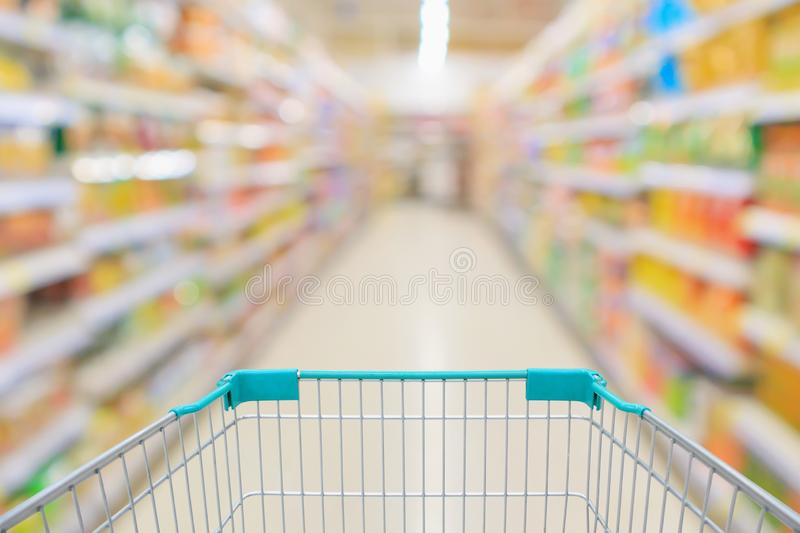 Supermarket aisle with empty shopping cart and product shelves interior blur background. Supermarket aisle with empty shopping cart and product shelves interior stock image