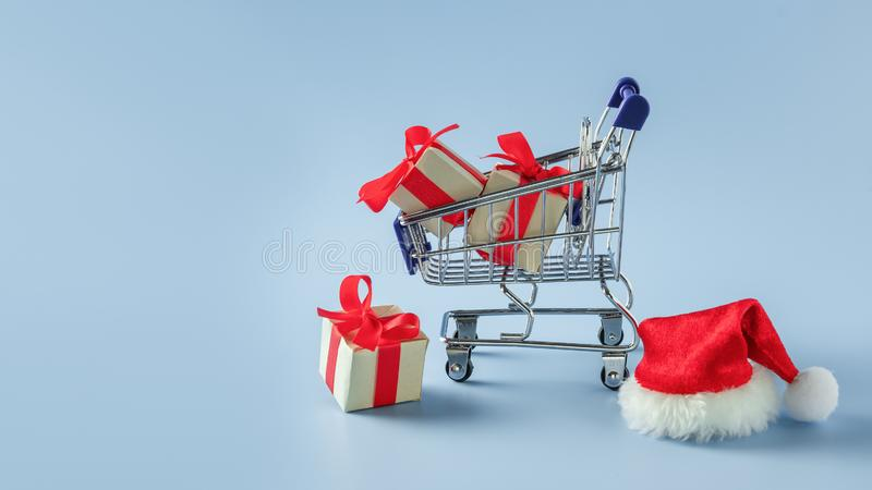 Supermarket cart with boxes and Santa hat on blue background. Concept: Christmas sale, delivery, shopping, gifts stock image