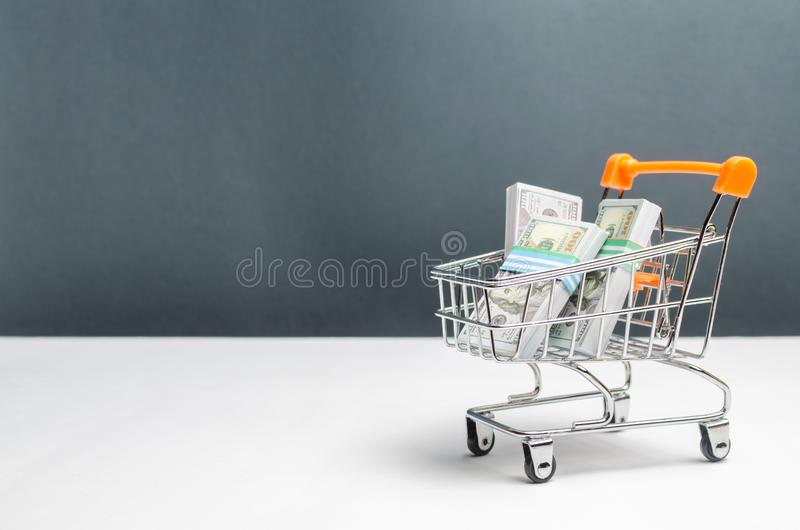 Supermarket cart with packs of dollars. The concept of microcredit and payday loans. Advertising financial services. Trap stock photography