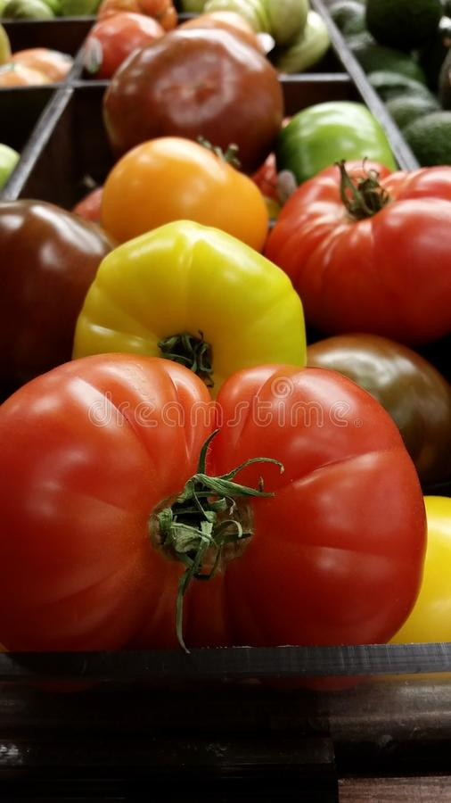 Supermarket: Fresh Heirloom Tomatoes. Grocery store produce section filled with colorful heirloom tomato varieties. These items tap into the current healthy stock photos