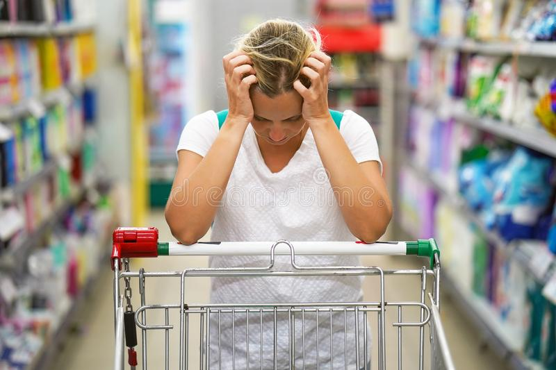 Supermarket girl with shopping trolley. Upset woman in a supermarket with an empty shopping trolley. Crises, rising prices for goods and products. Woman shopping royalty free stock photo