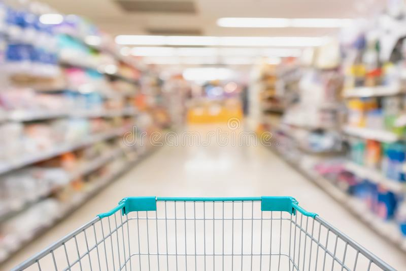 Supermarket grocery store aisle with empty shopping cart. Business concept stock image