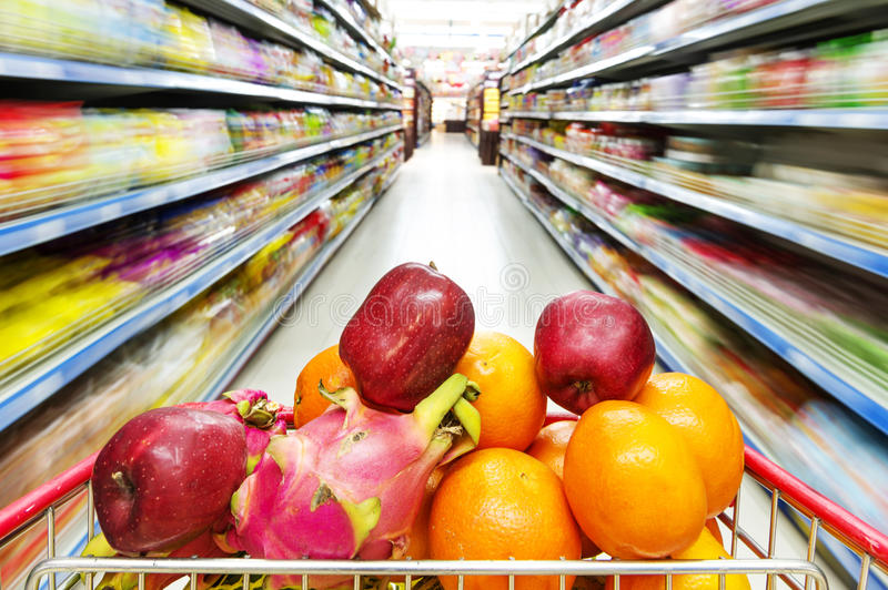 Supermarket interior, filled with fruit of shopping cart. royalty free stock images
