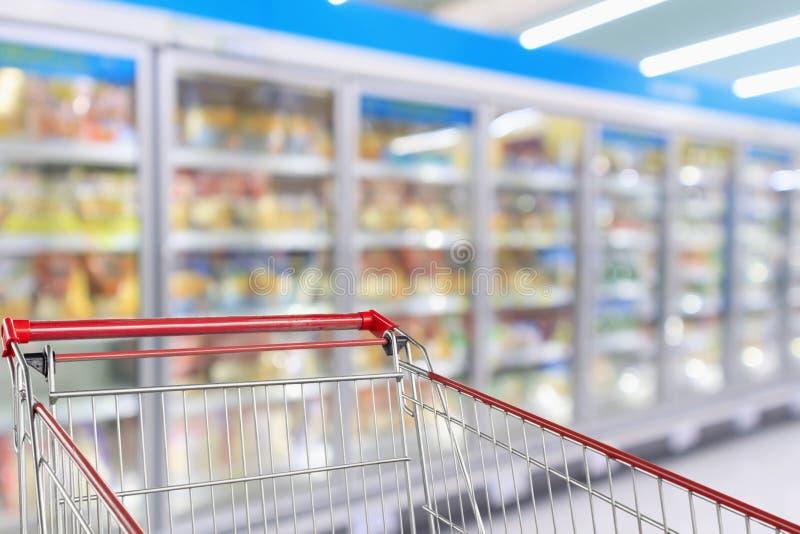 Blur Supermarket refrigerators freezer aisle. Supermarket refrigerators freezer aisle blur defocused background with empty red shopping cart stock image