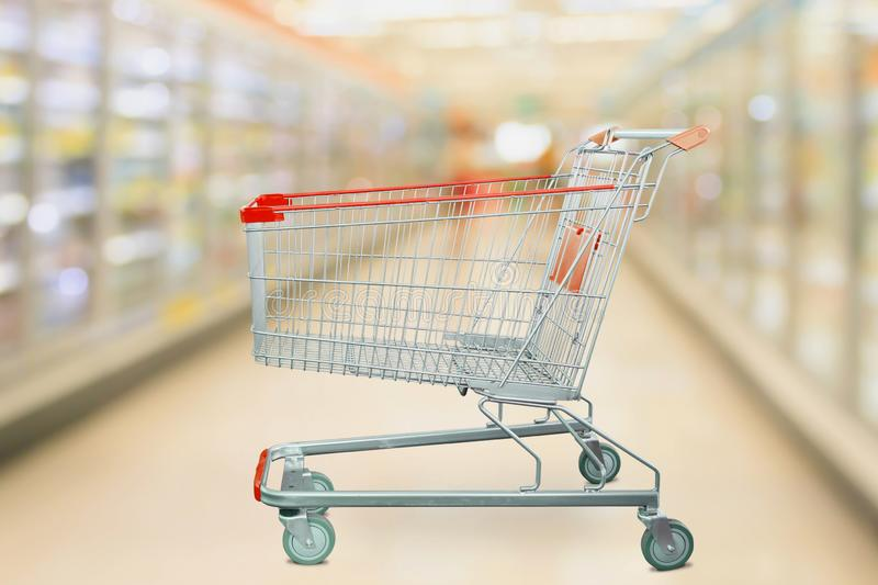 Supermarket refrigerators freezer aisle with empty red shopping cart. Supermarket refrigerators freezer aisle blur defocused background with empty red shopping stock images
