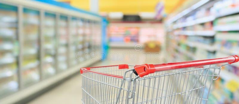 Supermarket refrigerators freezer aisle with empty red shopping cart. Supermarket refrigerators freezer aisle blur defocused background with empty red shopping royalty free stock photo