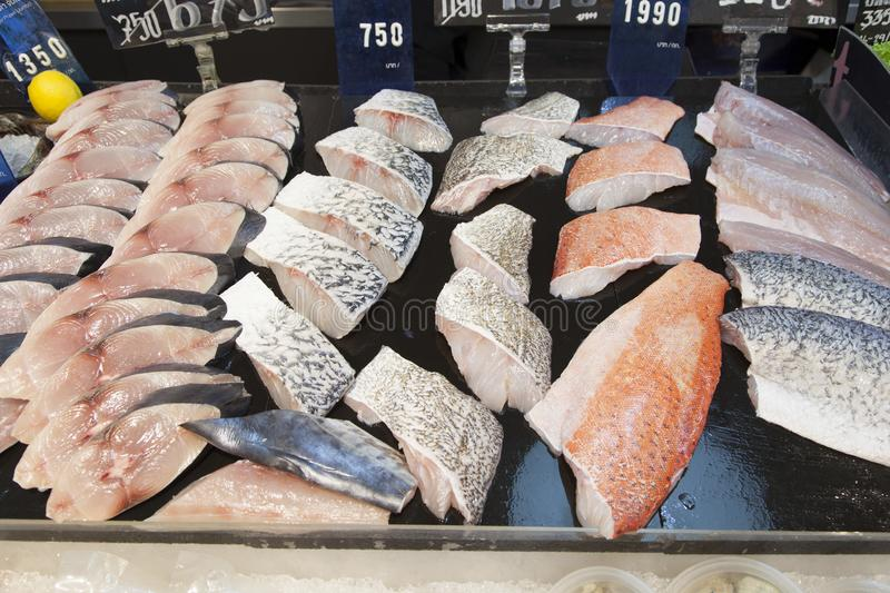 Supermarket stall with raw fish. Supermarket stall with Salomon and Coalfish Pollachius virens raw fish - fresh fish counter full with diverse - organic fish stock image