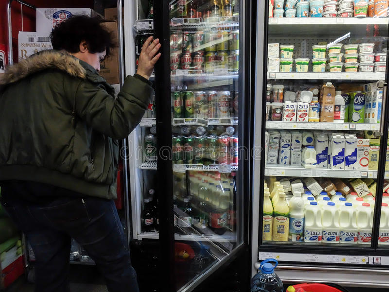 Supermarket week end shopping. Bucharest, Romania, December 24, 2015: A woman chooses beer from a freezer inside a supermarket in Bucharest royalty free stock image