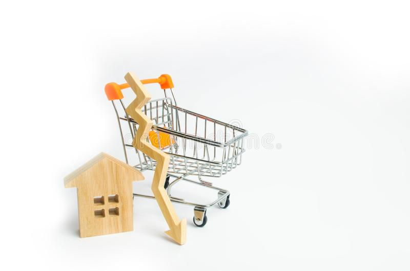 A supermarket wheelbarrow with a small house and a wooden arrow down on a white background. The fall in property prices. Decrease royalty free stock photo