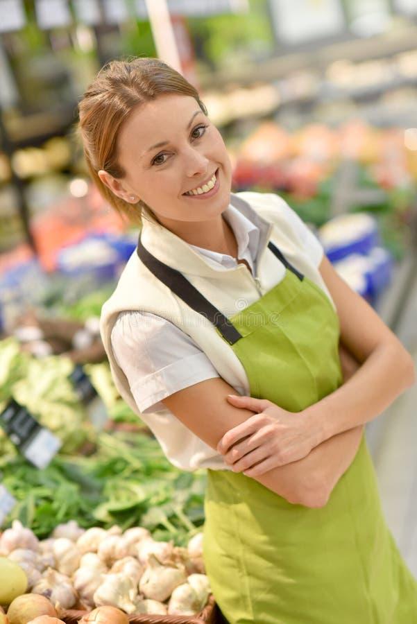 Supermarketanställd i grönsakavsnitt arkivfoto