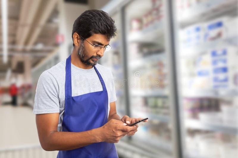 Supermarketanställd som smsar på telefonen royaltyfria foton