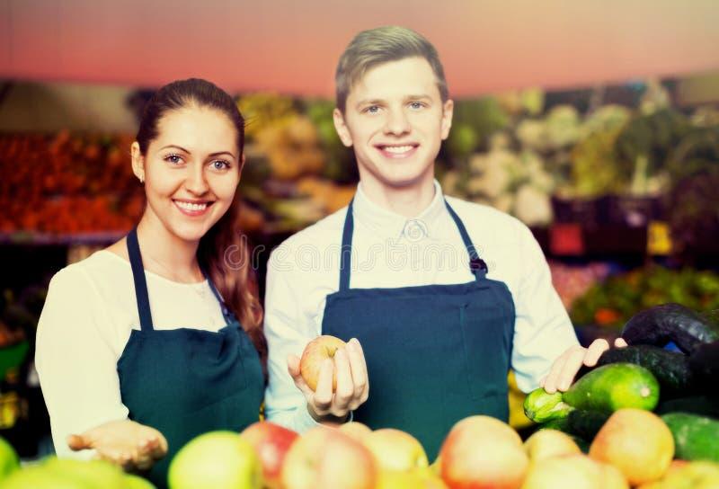 Supermarketarbetare som ordnar äpplen på skärm arkivfoto