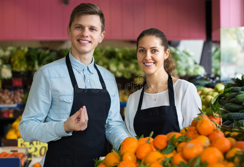 Supermarketarbetare som säljer apelsiner royaltyfri bild