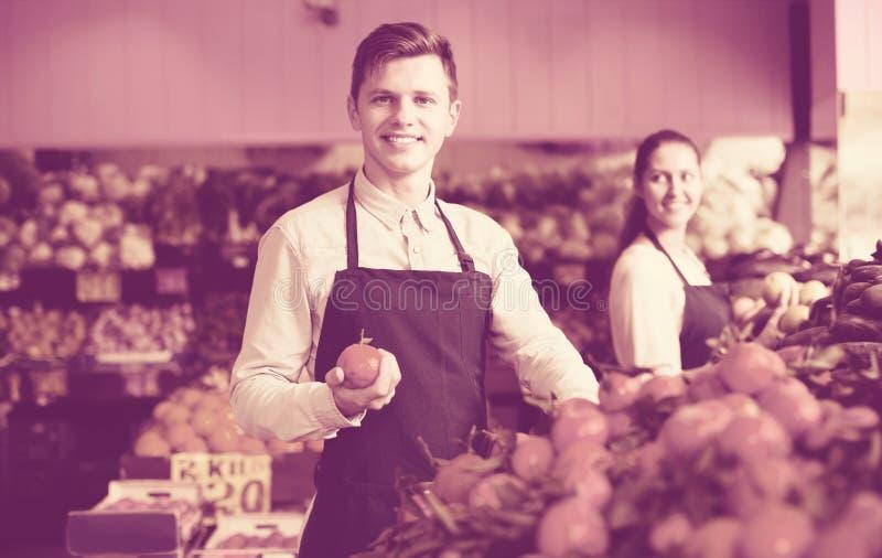 Supermarketarbetare som säljer apelsiner royaltyfri fotografi