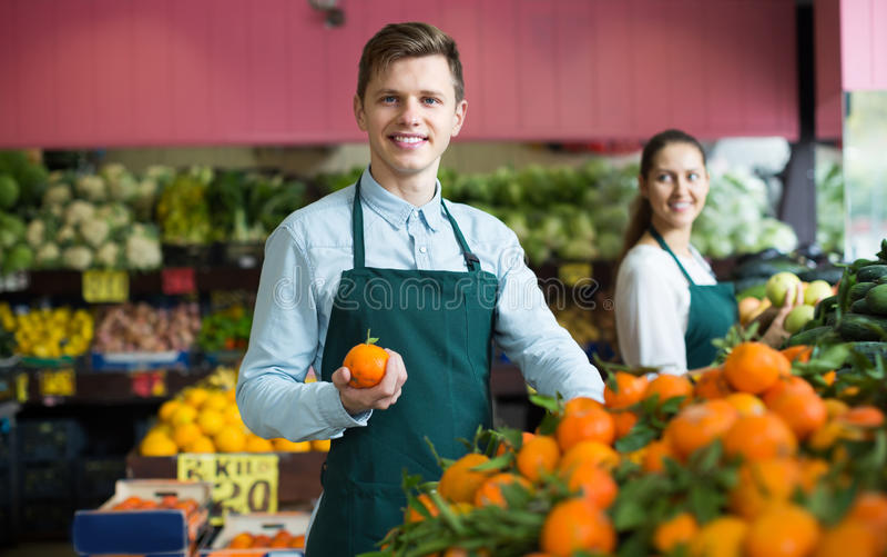 Supermarketarbetare som säljer apelsiner arkivbild
