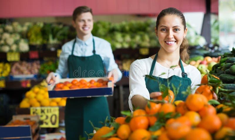 Supermarketarbetare som säljer apelsiner arkivfoto
