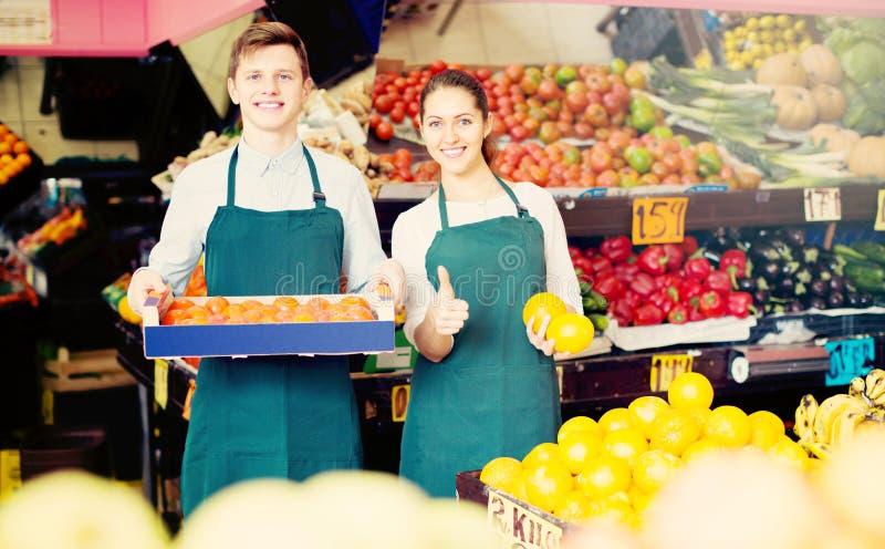 Supermarketarbetare som säljer frukter royaltyfria foton