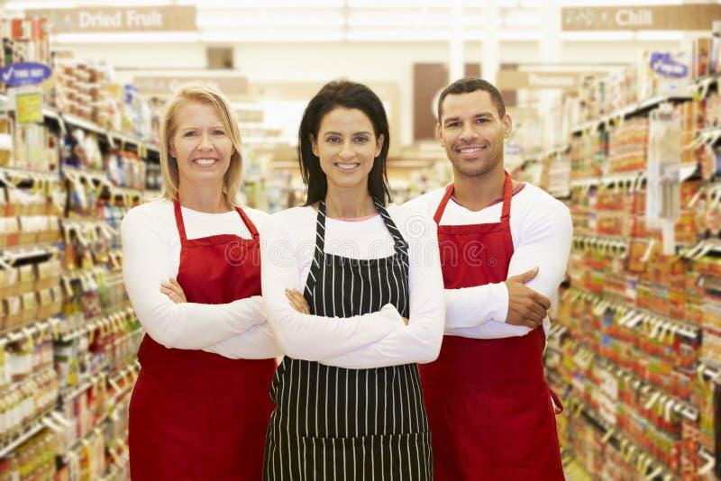 Supermarketarbetare som står i livsmedelsbutikgång royaltyfri foto