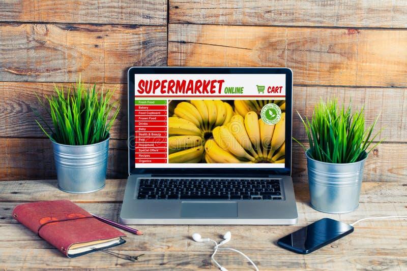 Supermarketlivsmedelsbutiken shoppar direktanslutet i en bärbar datorskärm på kontoret arkivbild