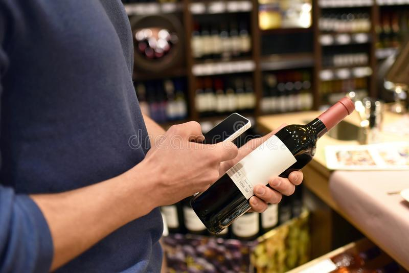 Supermarketshopping med smartphonen - prissätta jämförelsen och information royaltyfri fotografi