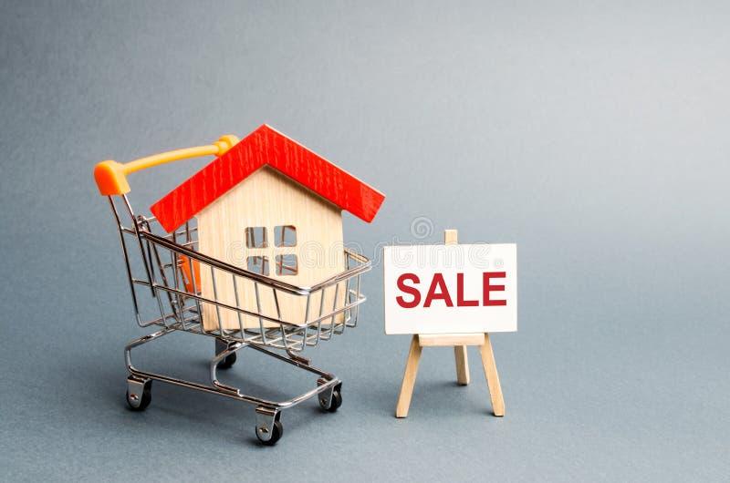 Supermarketvagn med hus och en Sale affisch Begreppet av att sälja ett hem, fastighetservice eller att köpa från ägaren royaltyfria bilder