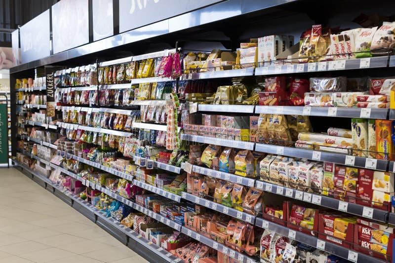 Supermarkt met planken van voedsel en dranken Merkur in Oostenrijk stock afbeeldingen
