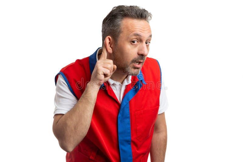 Supermarktangestellter, der Ohr als Hören berührt lizenzfreies stockfoto