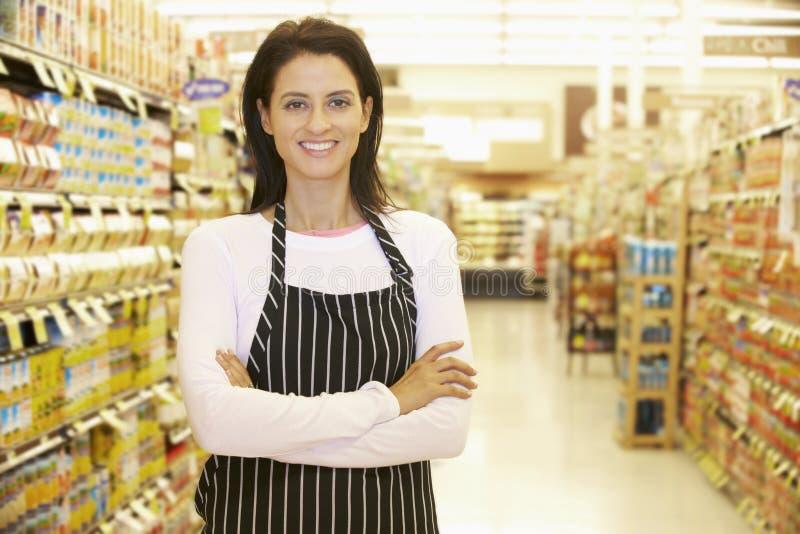 Supermarktarbeider die zich in Kruidenierswinkeldoorgang bevinden stock afbeelding