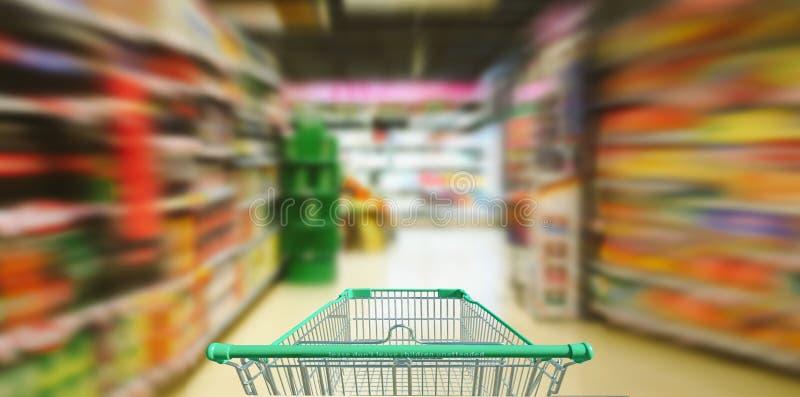 Supermarktgang mit leerem grünem Warenkorb stockfotografie
