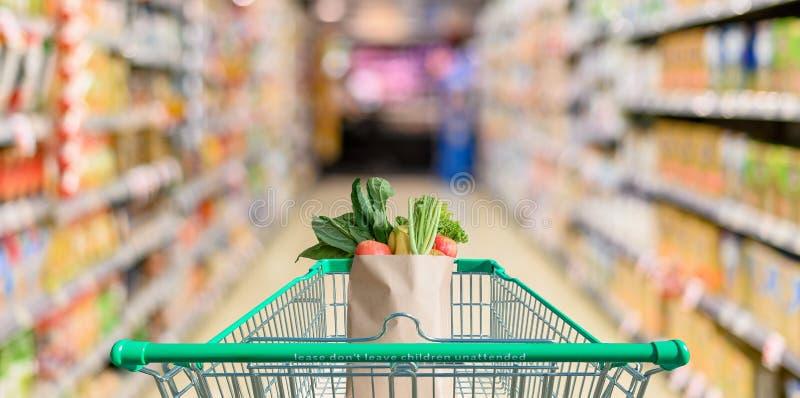 Supermarktgang mit leerem grünem Warenkorb stockbild