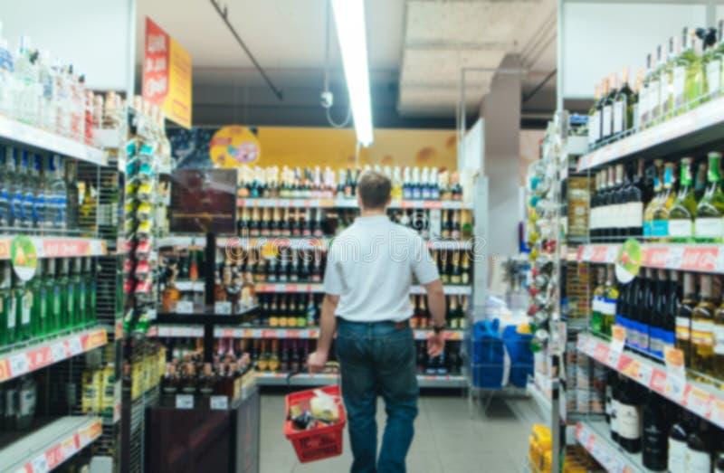 Supermercado borroso abstracto Un hombre con una cesta roja hace compras en la tienda El hacer compras en un supermercado fotos de archivo libres de regalías