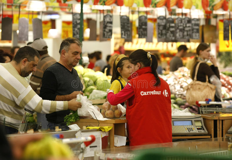Supermercado del cruce de las tiendas de comestibles de los clientes que hace compras imagenes de archivo