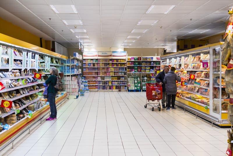 Supermercado grande Auchan de la comida con los clientes y productos y personal imagen de archivo libre de regalías